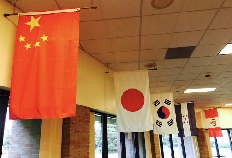 Flags representing each of the 17 countries of origin line the walls of the Hesston College cafeteria.
