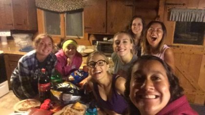 Members of the women's soccer team snap a selfie while munching on snacks in their cabin. Photo by Mika Matsuda
